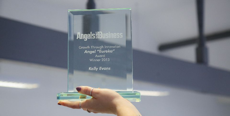 A hand holds up a glass Angels Business award.
