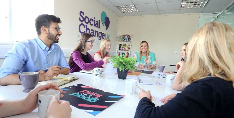 The Social Change UK team sit around the meeting room table, smiling and discussing ideas.