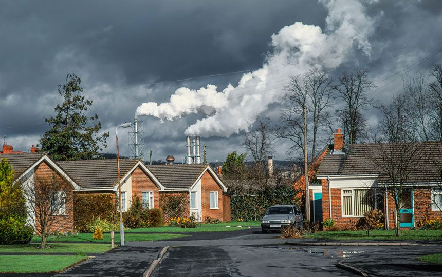 In the distance, behind a row of bungalows, are metal looking towers emitting a cloud of thick white smoke. The sky is grey and the ground is wet, as if it has been raining.