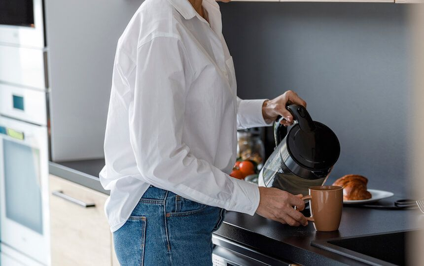 A woman is making a cup of tea in her kitchen.