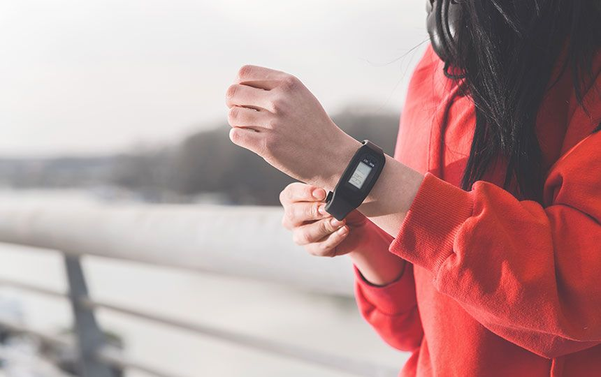 A woman in a red hooded jumper wearing a a black FitBit on her wrist.