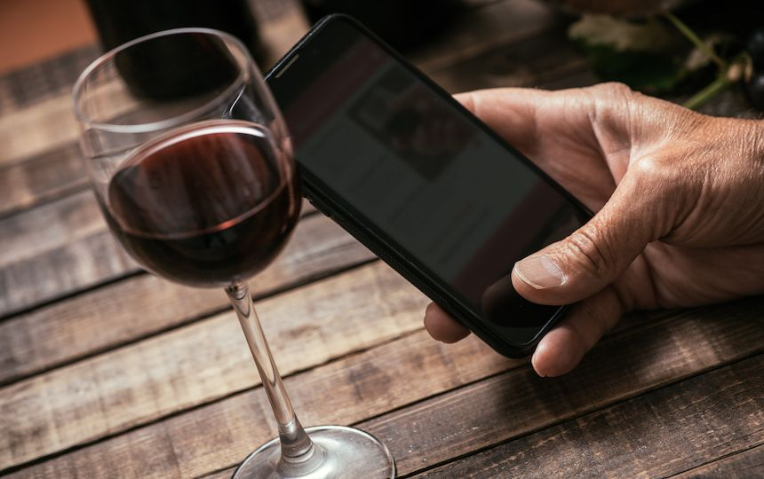 A hand holds a smart phone at a wooden table, with a small glass of red wine next to it.