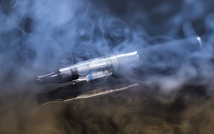 A black e-cigarette is visible through a cloud of vapour.