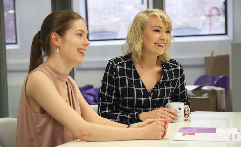 Chloe and Eloise sit in the Social Change UK meeting room, drinking tea and laughing.