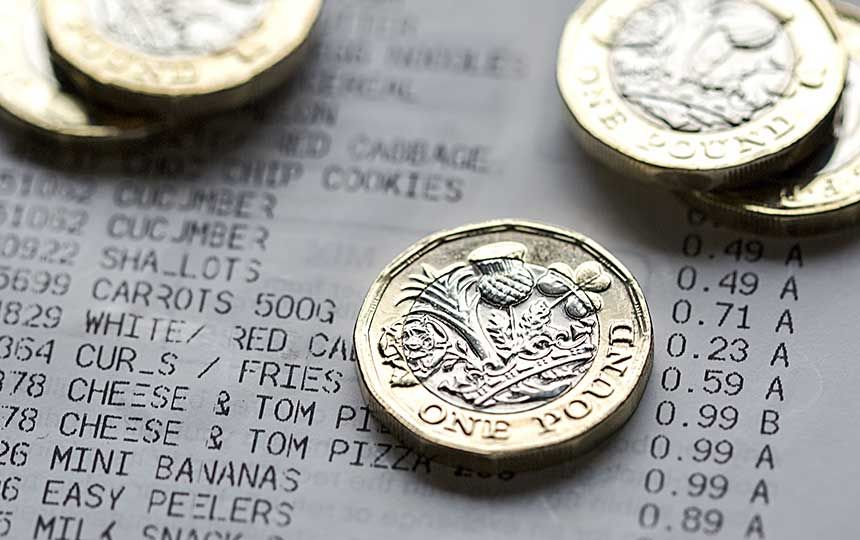 A close up image of five £1 coins on top of a receipt.