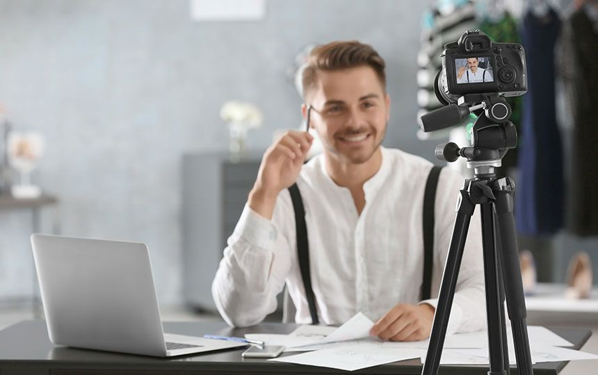 A man sat at a desk filming himself on a camera on a tripod, with his laptop in front of him.