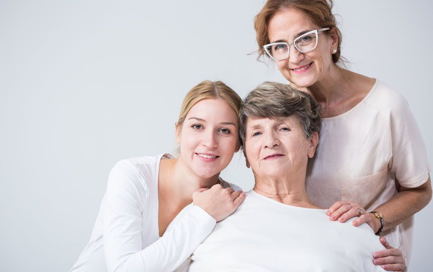 Three generations of women are smiling together; a mother, daughter and grandmother.
