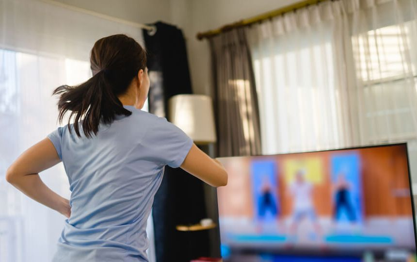 A woman is watching a tv screen in her living room, following an exercise routine.