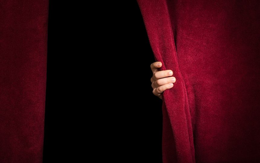 A pair of red velvet stage curtains are slightly open, with a hand holding the right curtain back slightly.