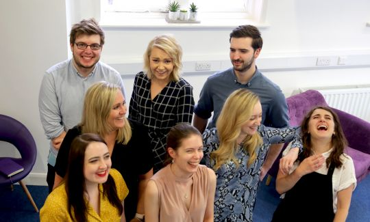 The Social Change UK team stand in a group laughing at each other, in the Social Change UK office.