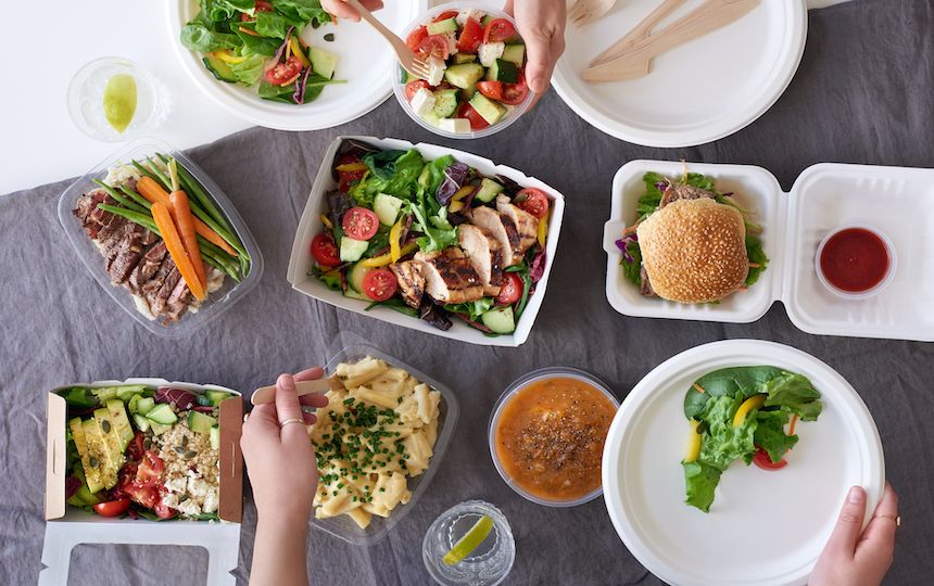 Hands reach for a range of colourful, healthy food dishes, including salads and pasta.