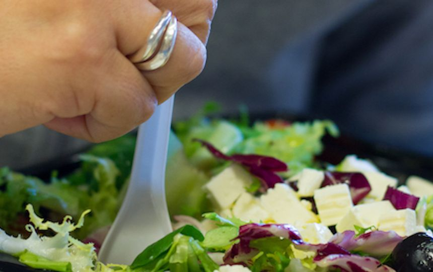 A hand is holding a plastic fork in a plastic container which is full of fresh salad.