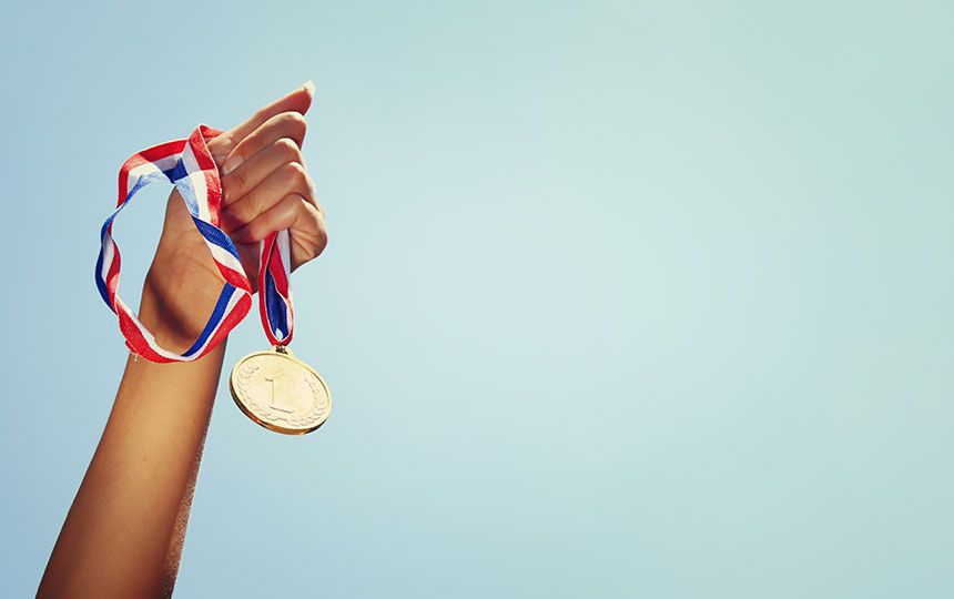 A hand against a blue sky, holding a first place medal.