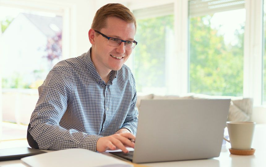 A man is smiling and looking engagingly towards his open laptop.