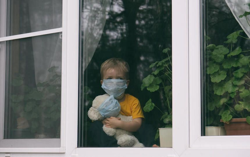 A young boy holds a teddy and stares out of a window. Both are wearing face masks.