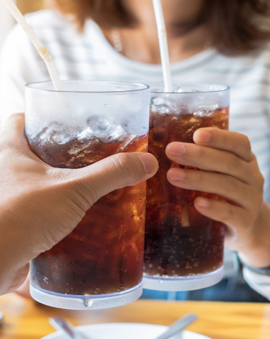 Two people clinking large glasses at a table, which are full of Coke, a straw and ice cubes.