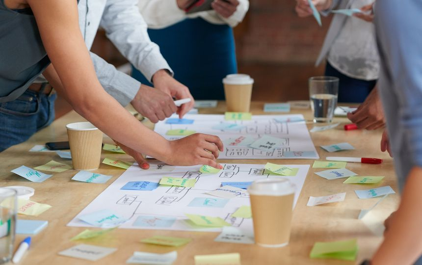 People are gathered around a table covered with sticky notes, diagrams and drinks.