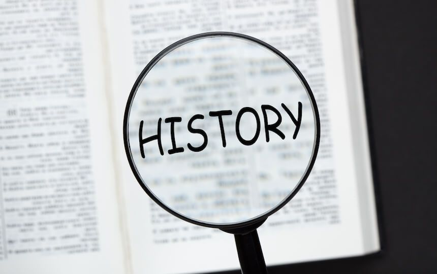 A large magnifying glass is held over an open book, magnifying the word 'History'.