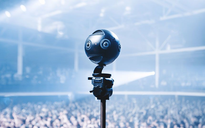 A small metal ball with built-in cameras and microphones is overlooking a large concert crowd.