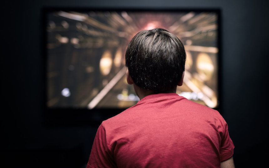 From behind, a young boy is playing a video game on his television in a dark room.
