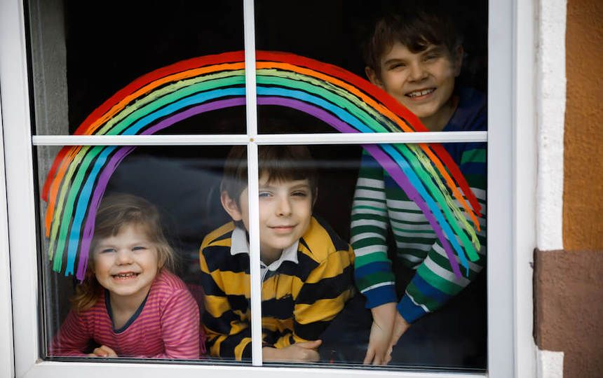 Three young children are smiling through a window painted with a rainbow.