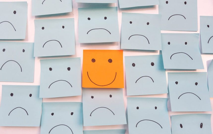 Numerous blue sticky notes with a sad face placed onto a wall and 1 orange note with a smiling face placed in the middle.
