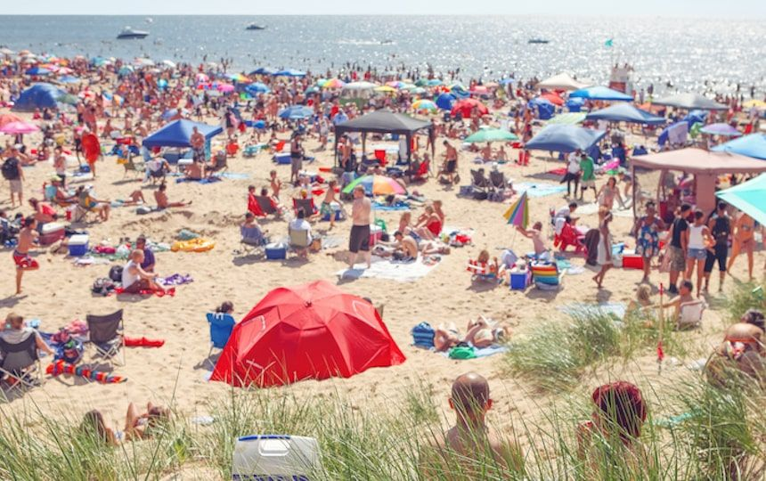A busy beach full of people with tents, towels and parasols on the sand and swimming.