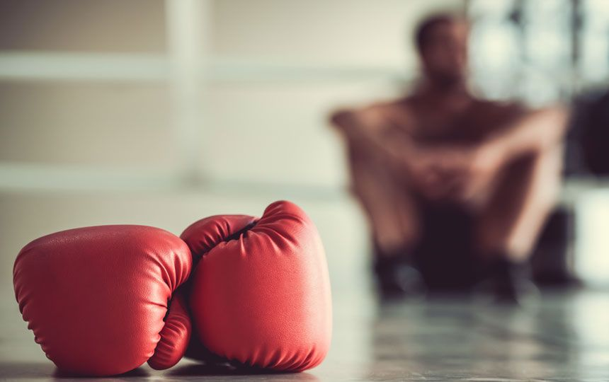 A pair of red boxing gloves lay on the floor and in the background is the blurred figure of someone sat on the floor with their legs pulled to their chest.