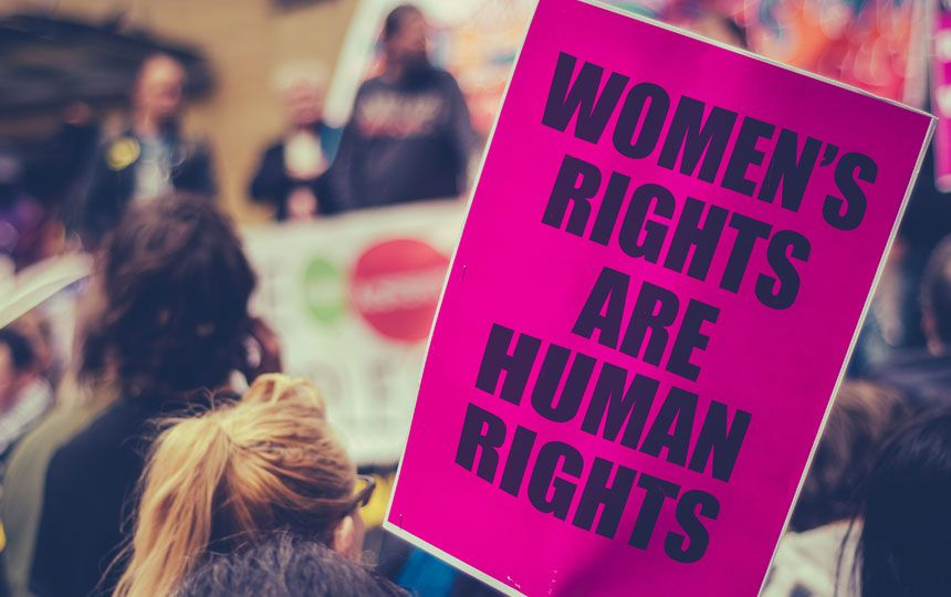 A large pink poster which says 'Women's rights are human rights' is shown at a march.