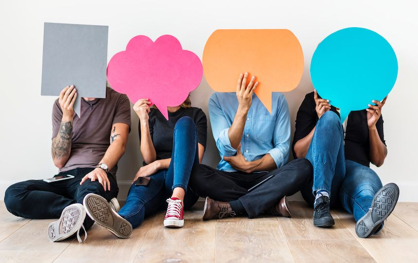 Four people are sat holding different shaped speech bubbles in front of their faces.