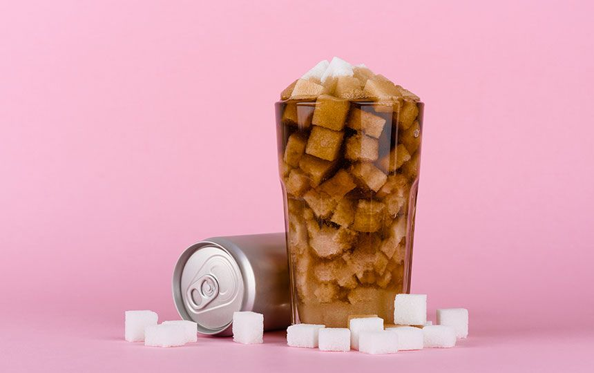 A can on its side is beside a glass overfilled with coke and sugar cubes.