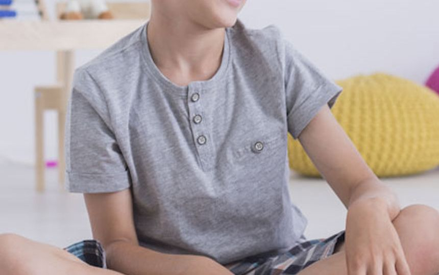 A young boy is sitting cross-legged on the floor in a bedroom, smiling off to the side.