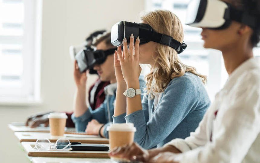 Four people are sat in a row, at separate desks and are wearing virtual reality headsets.