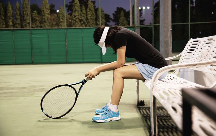 A woman holding a racquet is sat on a tennis court bench, looking downheartedly at the floor.