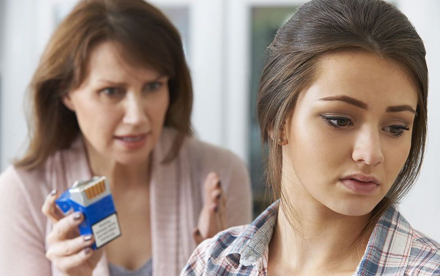 A young girl looks away from her mother, who angrily holds an open packet of cigarettes.