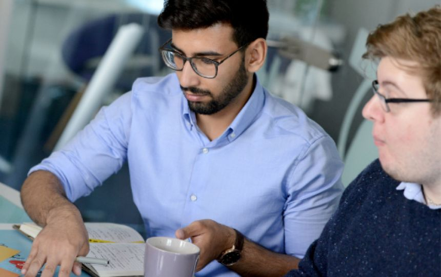 Bobby and Ammar sat at a desk reviewing work notes with a cup of tea