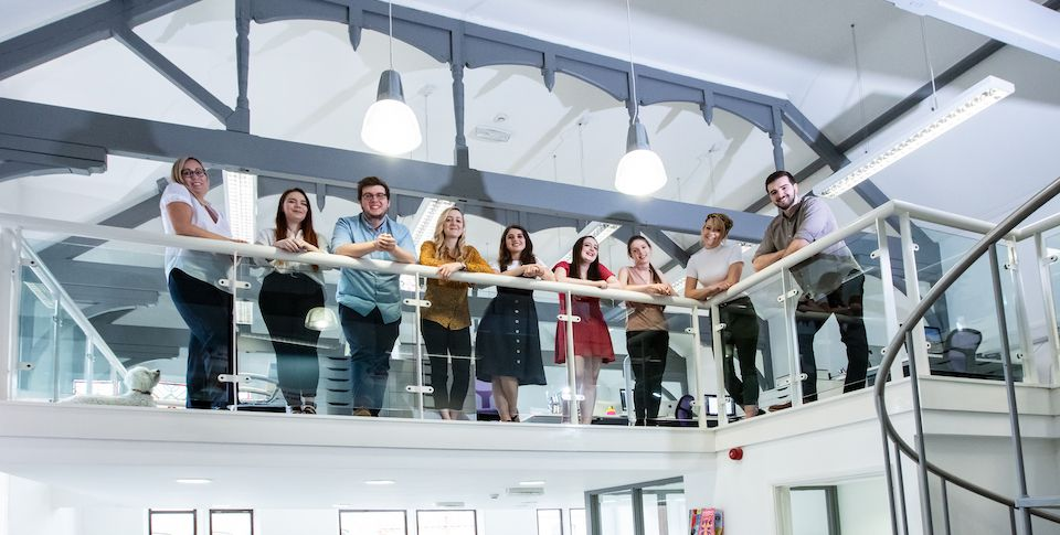 The Social Change UK team looking down and smiling from the office mezzanine.