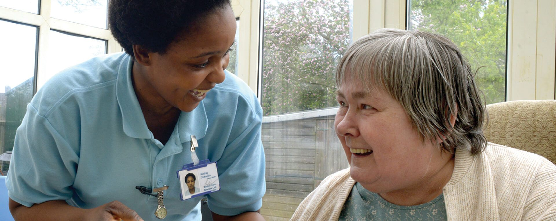 A caregiver and care user laughing and smiling with each other.
