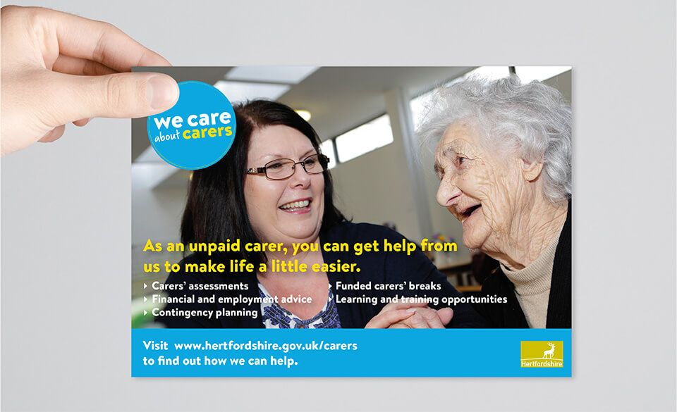A hand holding up a flyer depicting an elderly care user and her carer.
