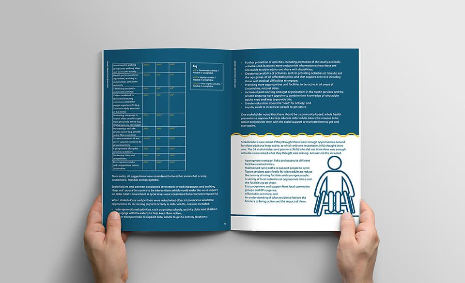 A person holding an open campaign report showing metrics and an illustration of a person in a wheelchair.
