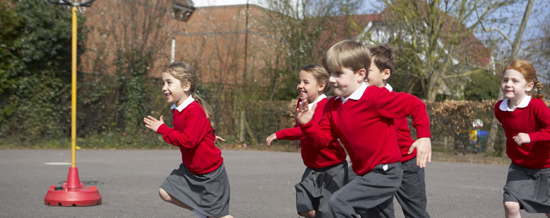 A group of school children in red jumpers running across the school's playground.