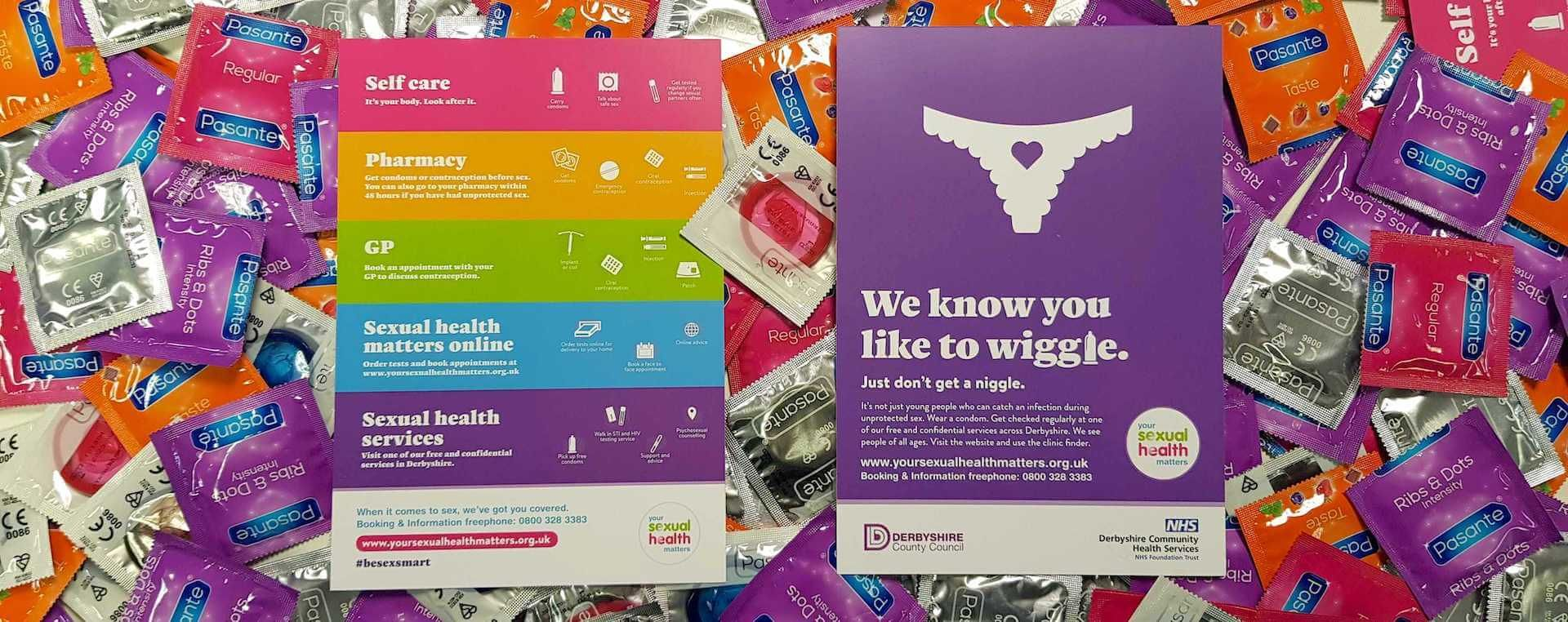 Brightly coloured flyers from the 'Your Sexual Health Matters campaign' on a pile of condoms.