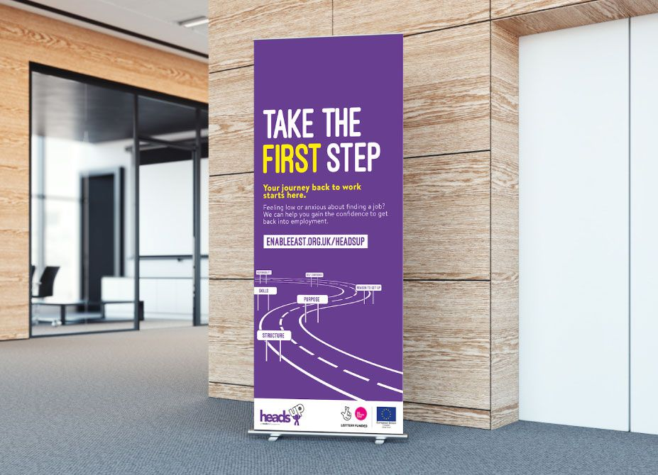 A HeadsUp branded roller banner placed in a corridor.