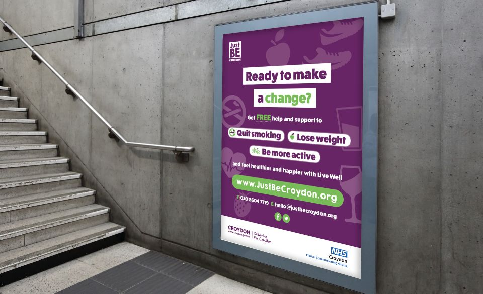 A JustBe Croydon billboard poster next to a concrete flight of stairs.
