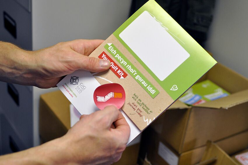 A man places a sticker seal onto one of the printed Quit Kits from the Quit for Them campaign.
