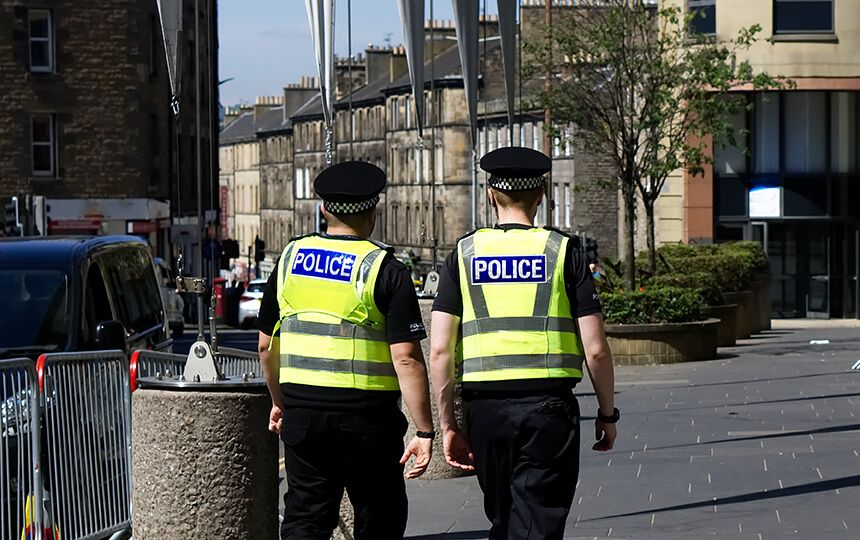 Two police officers patrolling together in a city centre street.