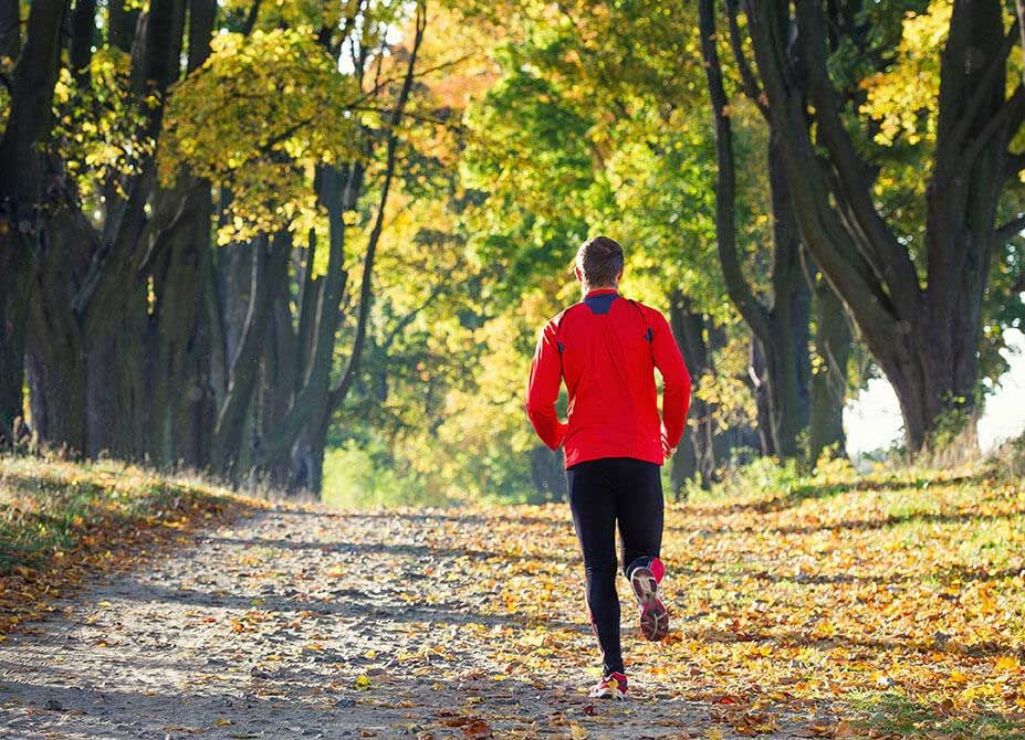 A young man wearing a red jacket running alone through a park.