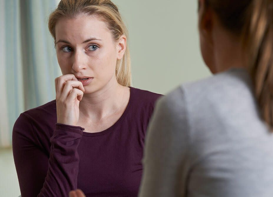A woman looks concerned and holds her face as she speaks to her therapist.