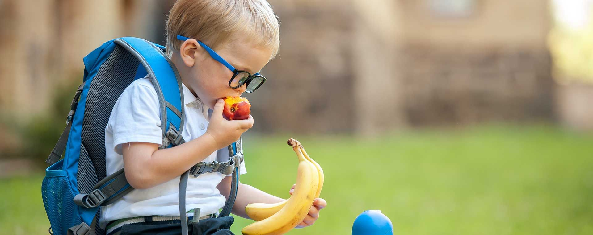 A young boy with glasses and a blue backpack is sat holding bananas and eating a nectarine.