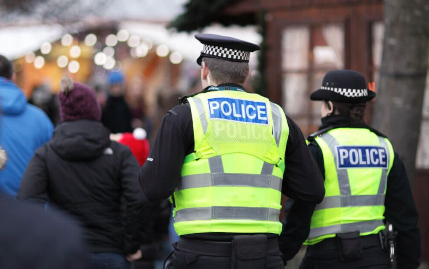Two police officers walking through a busy winter market event.